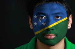 Portrait of a man with the flag of the Solomon Islands painted on his face on black background. The concept of sport or nationalism royalty free stock image