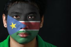Portrait of a man with the flag of the South Sudan painted on his face on black background. The concept of sport or nationalism stock photo