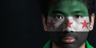 Portrait of a man with the flag of the Syrian Interim Government painted on his face on black background. The concept of sport or nationalism stock image