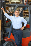 Portrait Of Man With Fork Lift Truck In Warehouse Stock Images