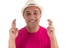 Hopeful man with crossed fingers. Latin American overweight. Whi. Portrait of man full of hope. Wishing you luck. He is wearing a pink T-shirt and white hat Royalty Free Stock Photos