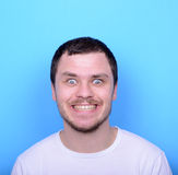 Portrait of man with funny face against blue background Royalty Free Stock Photo