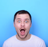 Portrait of man with funny face against blue background Royalty Free Stock Images