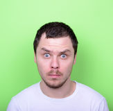 Portrait of man with funny face against green background. This image is made in studio with model standing against colored backgrounds.Set of various conceptual Stock Photo