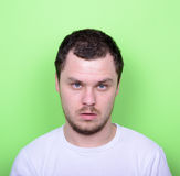 Portrait of man with funny face against green background. This image is made in studio with model standing against colored backgrounds.Set of various conceptual Royalty Free Stock Images