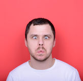 Portrait of man with funny face against red background. This image is made in studio with model standing against colored backgrounds.Set of various conceptual Royalty Free Stock Image