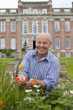 Portrait of man gardening with manor in background Royalty Free Stock Photo