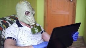 Portrait of a man in gas mask or respirator and gloves with a laptop at home