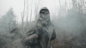 Man in gas mask standing on old railway in cloud of toxic smoke. Stalker concept