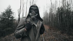 Portrait man in gas mask standing on railway in dead forest. Post apocalypse