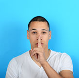 Portrait of man with gesture for silence against blue background Stock Photo