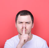 Portrait of man with gesture for silence against red background Stock Photography