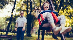 Portrait of man and girl with down syndrome swinging Royalty Free Stock Photos