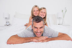 Portrait of a man giving a piggy back to his children Royalty Free Stock Photos