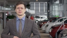 Portrait of man in gray jacket and blue shirt at auto dealer car center. slow motion. stock video