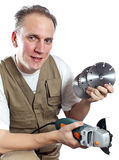 Portrait of the man in green working overalls and a white t-shirt with the construction tool in hands o Stock Photos