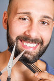 Portrait of a man grooming his beard with scissors Stock Images