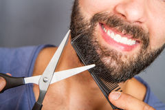 Portrait of a man grooming his beard with scissors Royalty Free Stock Images