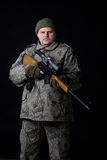 Portrait of a man with a gun on a black. Royalty Free Stock Photos