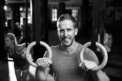 Portrait Of Man In Gym Exercising With Gymnastic Rings Royalty Free Stock Photography