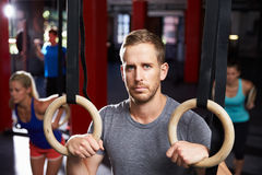 Portrait Of Man In Gym Exercising With Gymnastic Rings Royalty Free Stock Images