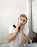 Portrait of man with hairbrush grimacing in bathroom Stock Photography