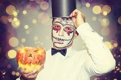 Portrait of man for Halloween party. Beautiful halloween man with burning pumpkin in hand. Halloween party concept. Royalty Free Stock Image