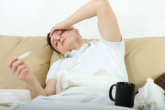 Portrait of man with headache lying sick in bed Stock Images