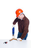 Portrait of man in helmet drilling a plank of wood Royalty Free Stock Photos