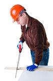 Portrait of man in helmet sawing plank of wood Royalty Free Stock Images