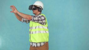 Man in a helmet and uniform uses a VR helmet. Portrait of a man in a helmet and uniform uses a VR helmet isolate on blue background stock footage