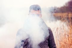 Man hiding in the fog in front of lake. Portrait of man hiding in the fog in front of lake royalty free stock photos