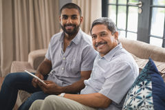 Portrait of man with his father sitting on couch at home. Portrait of smiling men with his father sitting together on couch at home Royalty Free Stock Image