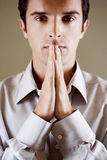 Portrait of a man with his hands in a praying position stock photo