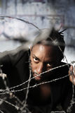 Portrait of a man holding barbed wire. And a graffiti wall in background stock photography