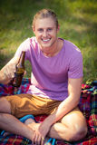 Portrait of man holding beer bottle at campsite. On a sunny day royalty free stock images
