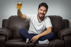 Portrait of a man holding bottle of beer and watching tv Stock Photo