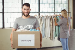 Portrait of man holding clothes donation box in office Stock Image