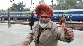 Portrait of man holding his hands widely spread at train station in Amritsar. AMRITSAR, INDIA - 2 MARCH 2015: Portrait of man holding his hands widely spread at stock footage