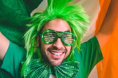 Portrait of a man holding the Irish flag. While wearing Saint Patrick`s day accessories royalty free stock photography