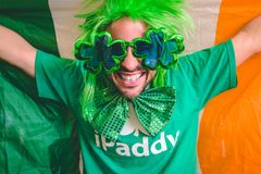 Portrait of a man holding the Irish flag. While wearing Saint Patrick`s day accessories stock photos