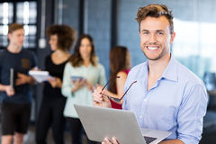 Portrait of man holding a laptop and smiling Stock Photo