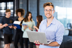 Portrait of man holding a laptop and smiling Stock Image