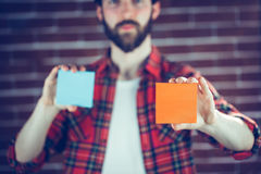 Portrait of man holding orange and blue adhesive notes Stock Images