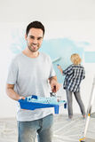 Portrait of man holding paint roller and tray with woman painting wall in background Stock Images