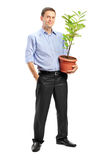 Portrait of a man holding a pot with plant. Full length portrait of a smiling man holding a pot with decoration plant on white background Royalty Free Stock Image