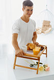Portrait of man holding tray with breakfast Royalty Free Stock Photo