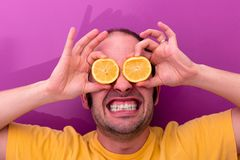 Portrait of a man holding two sliced lemons in his eyes royalty free stock photo