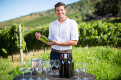 Portrait of man holding wine bottle by table at vineyard Royalty Free Stock Photography