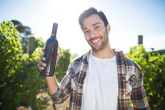 Portrait of man holding wine bottle at vineyard Stock Photo